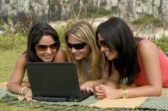 Mujeres y computadora portátil en la playa Fotos de archivo