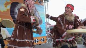 Mujeres y hombres en el baile nacional de Kamchatka de los habitantes indígenas de la ropa con pandereta