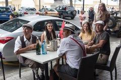 Mujeres y hombres que se sientan en una tabla con ropa del vintage Fotos de archivo