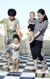 Mujeres y juego de niños asiáticos con el agua Imagenes de archivo