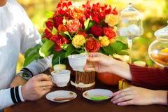 Mujeres y las manos de los hombres con los anillos de bodas con dos tazas de té Imagenes de archivo