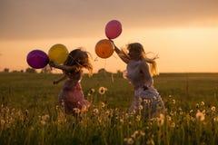 mujeres y muchacha que saltan con los globos al aire libre Fotografía de archivo libre de regalías
