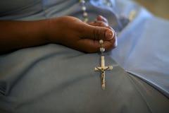 Mujeres y religión, hermana católica que ruega en la iglesia, sosteniendo c Imagen de archivo