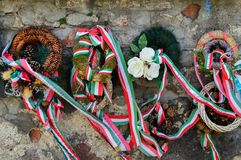 MUKACHEVO, UKRAINE - AUGUST 23 , 2017 , Ribbon with national colours of Hungary tied up to the flower tribute standing near to the. Castle wall in Mukachevo Royalty Free Stock Photos