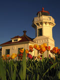 Mukilteo Lighthouse 2. The evening sun shining on the lighthouse at Mukilteo, Washington against a deep blue sky with yellow and orange tulips in the foreground stock images