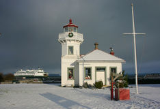 Mukilteo lighthouse. The lighthouse does it's job, as the ferry comes to terminal on a cold and snowy morning Stock Photo