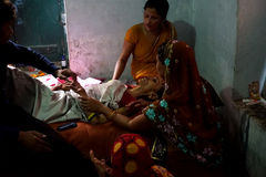 Mukti Bhawan, Varanasi. MP053: Relatives sit beside a dying woman at Mukti Bhawan complex or Moksha Bhavan or Salvation House. The hostel where people check-in Royalty Free Stock Photos
