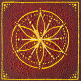 Muladhara root chakra. Hand painted mandala with yellow white and red colours on a piece of square wood Stock Image