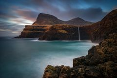 Mulafossur on Vagar. Mulafossur waterfall on Vagar Island in colorful sunset, Faroe Islands stock image