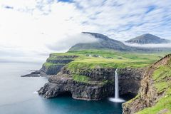 Mulafossur Waterfall with Gasadalur village in the background in. Vagar island, amazing spectacular landscape in the Faroe Islands destination in the middle of Stock Photography