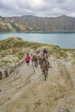 Mulas que montan de la gente en el camino en el lago Quilotoa, Ecuador Imágenes de archivo libres de regalías