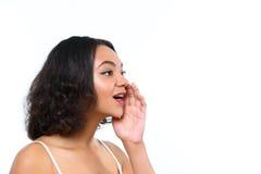 Mulatmeisje die met hand dichtbij haar mond roddelen royalty-vrije stock foto