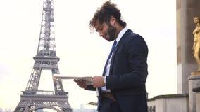 Mulattezeitungsmannlesezeitungsartikel nahe Eiffelturm stock footage