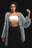 Mulatto alla moda in pelliccia che tiene la sua acconciatura della treccia su fondo nero Ragazza di Amarican dell'Africano con ca Fotografia Stock Libera da Diritti