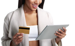 Mulatto black woman holding digital tablet computer and pay from gold credit card. Close-up view.  on white. Mulatto black woman holding digital tablet computer Stock Photo