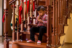 Mulatto child plays wind instrument. Royalty Free Stock Photo