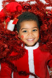 Mulatto child on a White background. Dressed as Santa Claus Stock Image