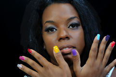 Mulatto girl with colorful fingernails Stock Images