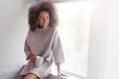 Mulatto girl drinking coffee on a windowsill Stock Photos