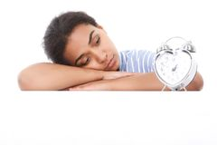 Mulatto girl leaning and looking at alarm clock Royalty Free Stock Photos