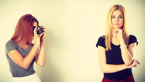 Mulatto girl photographing blonde woman. Photographer and model. Mulatto girl shooting images, taking photos with camera, photographing blonde woman Stock Image
