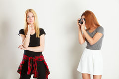 Mulatto girl photographing blonde woman. Photographer and model. Mulatto girl shooting images, taking photos with camera, photographing blonde woman Royalty Free Stock Images