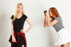 Mulatto girl photographing blonde woman. Photographer and model. Mulatto girl shooting images, taking photos with camera, photographing blonde woman Stock Photography