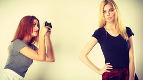 Mulatto girl photographing blonde woman. Photographer and model. Mulatto girl shooting images, taking photos with camera, photographing blonde woman Royalty Free Stock Photos