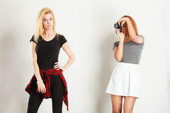 Mulatto girl photographing blonde woman. Photographer and model. Mulatto girl shooting images, taking photos with camera, photographing blonde woman Stock Images