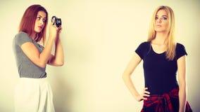 Mulatto girl photographing blonde woman Stock Photo