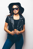 Mulatto girl wearing sunglasses and black hat over a white background. Stock Photos