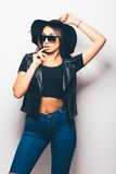 Mulatto girl wearing sunglasses and black hat over a white background. Beautiful fashion mulatto girl wearing sunglasses and black hat over a white background Stock Photography