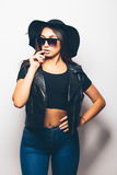 Mulatto girl wearing sunglasses and black hat over a white background. Beautiful fashion mulatto girl wearing sunglasses and black hat over a white background Stock Photos