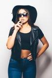 Mulatto girl wearing sunglasses and black hat over a white background. Beautiful fashion mulatto girl wearing sunglasses and black hat over a white background Stock Photo