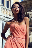 Mulatto girl wears elegant coral dress with bijou ,posing beside antic palace Royalty Free Stock Photo