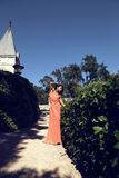 Mulatto girl wears elegant coral dress with bijou ,posing beside antic palace Stock Photos