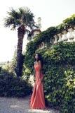 Mulatto girl wears elegant coral dress with bijou ,posing beside antic palace Royalty Free Stock Photos
