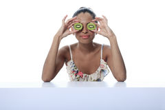 A mulatto person having two kiwi in front of the Stock Images
