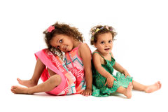 Mulatto sisters are sitting back to back playing. Girls in red and green dress are playing, smiling and showing sister love and happiness. A girl is missing Royalty Free Stock Photography