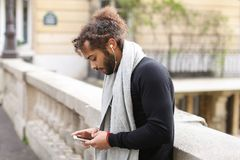 Half African tourist listening to new songs in earphones with sm. Mulatto tourist raving with white in ear headphones and smartphone near Eiffel tower. Jocund Stock Photo