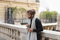Half African tourist listening to new songs in earphones with sm. Mulatto tourist raving with white in ear headphones and smartphone near Eiffel tower. Jocund Stock Image