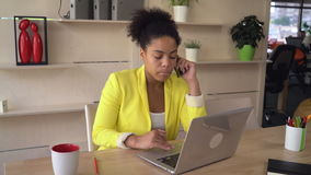 Mulatto using computer talking with client stock footage