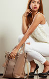 Mulatto woman holding beige leather bag. Royalty Free Stock Photography