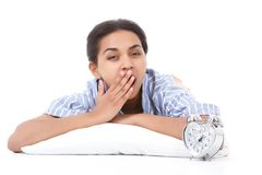 Mulatto woman lying and yawning. Looking exhausted. Portrait of youthful mulatto girl lying on white pillow against isolated background and yawning Royalty Free Stock Photo