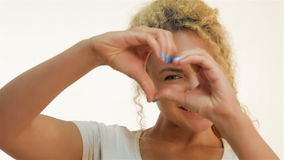 Mulatto woman showing heart shape gesture. Mulatto girl showing heart shape gesture and smiling at the camera. Attractive young girl on a white background stock footage