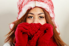 Mulatto woman wearing warm winter clothing, closeup. Winter clothing, fashion concept. Closeup of young mulatto woman covering her face with hands wearing red Stock Photos