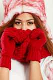 Mulatto woman wearing warm winter clothing, closeup. Winter clothing, fashion concept. Closeup of young mulatto woman covering her face with hands wearing red Royalty Free Stock Images