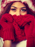 Mulatto woman wearing warm winter clothing, closeup. Winter clothing, fashion concept. Closeup of young mulatto woman covering her face with hands wearing red Stock Image