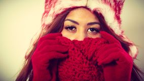 Mulatto woman wearing warm winter clothing, closeup. Winter clothing, fashion concept. Closeup of young mulatto woman covering her face with hands wearing red Royalty Free Stock Photos