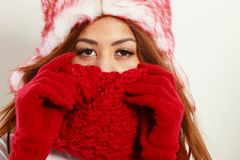 Mulatto woman wearing warm winter clothing, closeup. Winter clothing, fashion concept. Closeup of young mulatto woman covering her face with hands wearing red Royalty Free Stock Photography